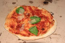 Pizzabrot mit Basilikum und Parmesan auf Pizzastein.