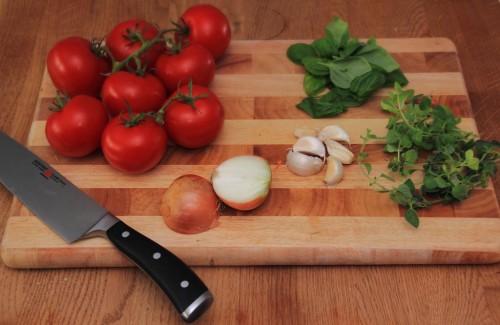 Zutaten für Tomatensoße bestehend aus frischen Rispentomaten, Basilikum, Oregano, Knaublauch und einer Zwiebel.