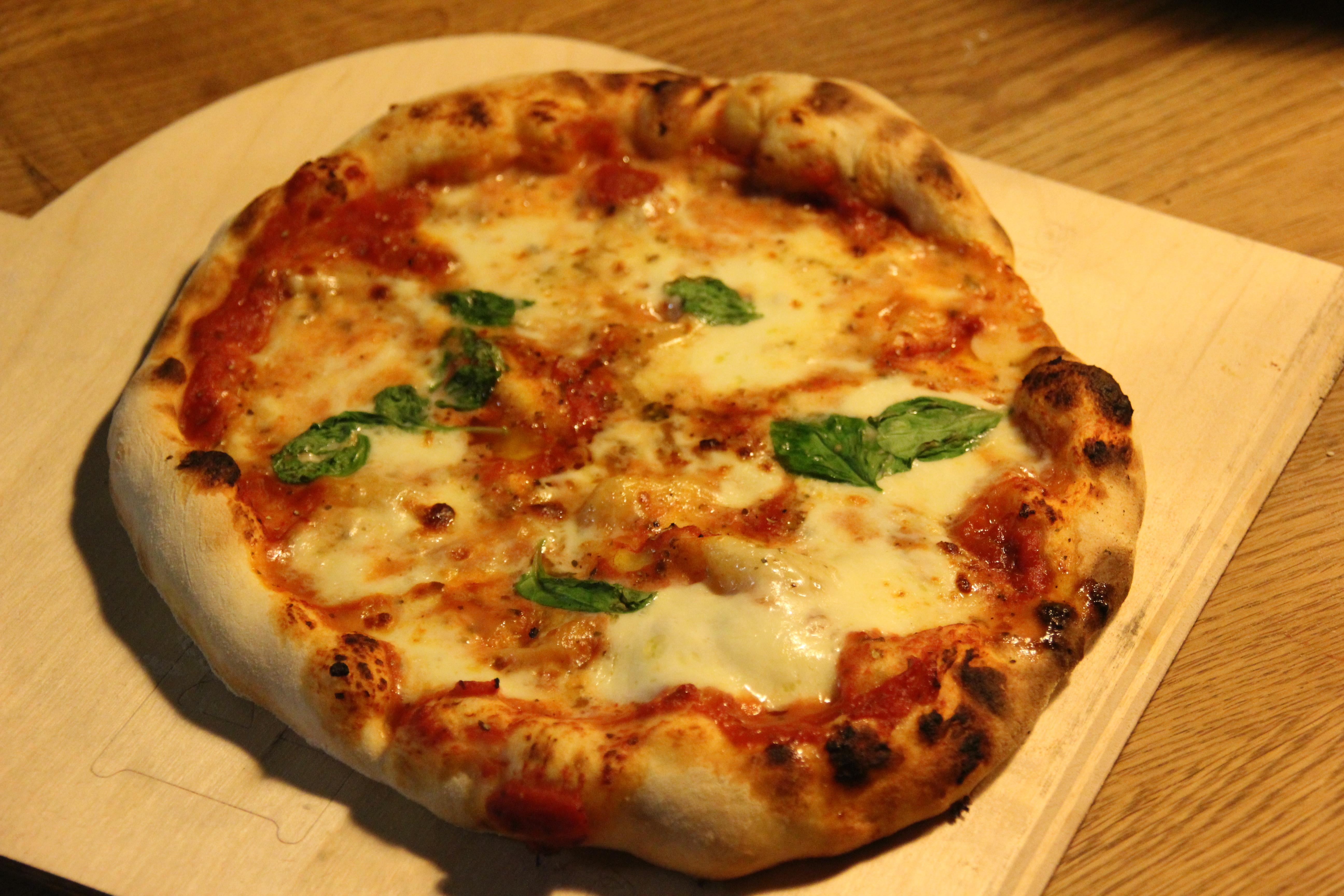 Pizza Margherita mit Mozzarella-Käse, Tomatensoße und frischem Basilikum
