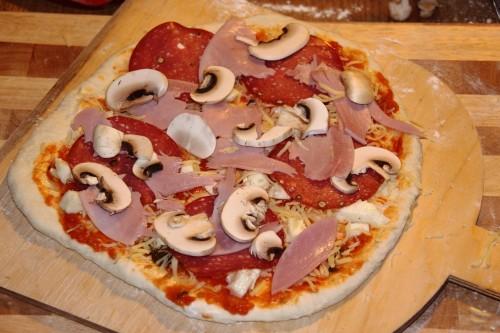 Vor dem Backen ist der Rand bei dieser Pizza Speciale mit Schinken, Käse und Pilzen noch kaum zu sehen. Erst beim Backen geht der Teig deutlich auf.