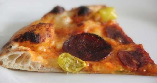 Leckers Stück Pepperoni Pizza mit grünen Chilis
