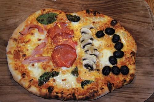 Silvesterpizza mit dem Schriftzug 2012 aus den Zutaten Schinken, Salami, Pilzen und Oliven.